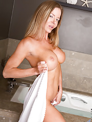 Amber Michaels peels off her towel to show her gigantic tits and pierced pussy