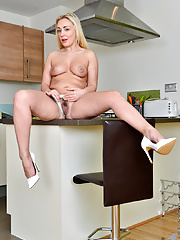 Blonde MILF undresses for nude posing in kitchen