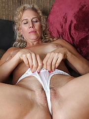 Busty blonde housewife Cally Jo fingers her pussy on the sofa