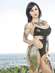 Busty tattoed MILF displaying her massive ass and perfect body