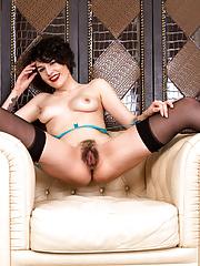 Cathy Heaven busty hottie in stockings spreads on a sofa