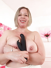 Fatty mature with big boobs plays with a dildo in a bald cunt