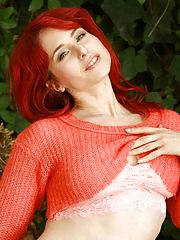 Horny redhead Andrea Rosu posing naked on a hay bail