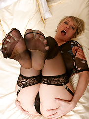 Hot mature babe Dee Williams poses erotically in black stockings