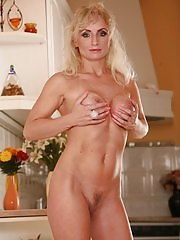 Older babe Kyra Blond fingers her pussy in the kitchen
