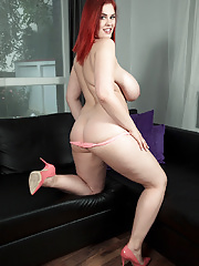 Redhead pornstar Alexsis Faye taking off her shorts with massive knockers