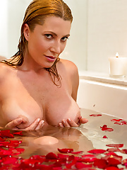 Romantic look at a housewife soaking in a tub full of rose petal