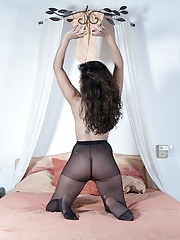 Sally strips off stockings while laying in her bed