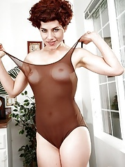 Short haired redhead mature in bodystocking stretches pink pussy